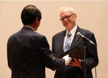 槇野学長(左)から博士記を受け取るホプキンス教授