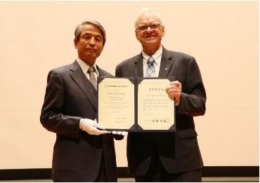 名誉博士記を掲げるホプキンス教授(右)と槇野学長