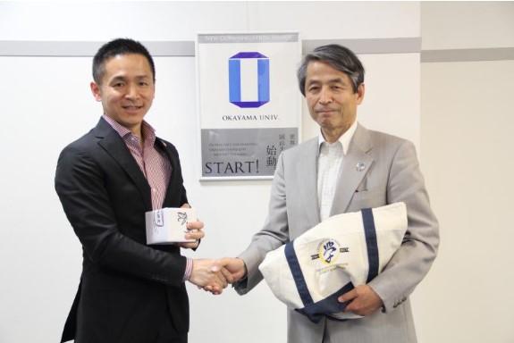 握手を交わす筒井所長(左)と槇野学長