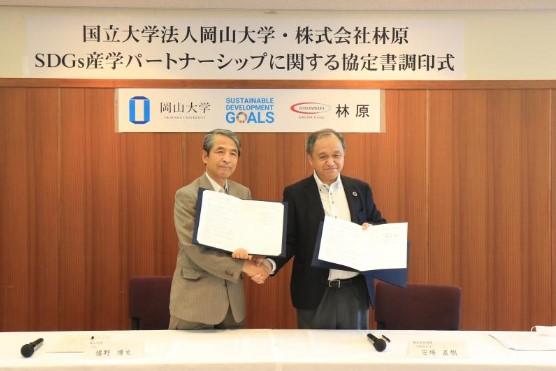 協定書を手に固く握手を交わす安場社長(右)と槇野学長 ※撮影時のみマスクを外しました