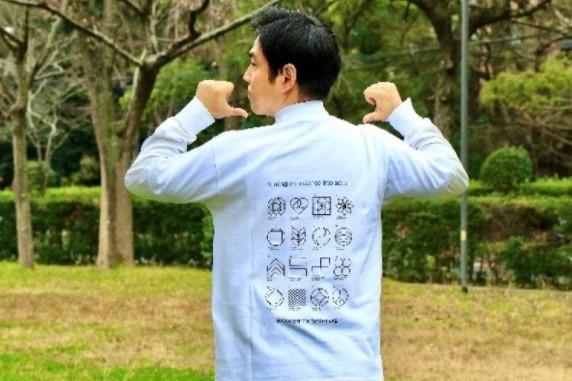 Tシャツを着て新ビジュアルアイコンをPRする横井副学長(後面)