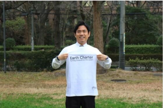 Tシャツを着て新ビジュアルアイコンをPRする横井副学長(前面)